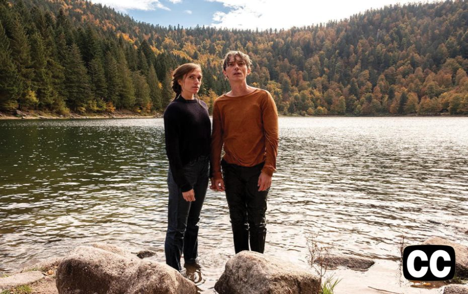 Closed captioned.  Watch trailer.  A man and a woman standing on the rocky bank of a river, with mountains in the background