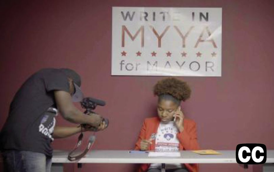 """Watch trailer.  Woman on cell phone being photographed, sitting at table underneath a sign that reads """"WRITE IN MYYA FOR MAYOR"""""""