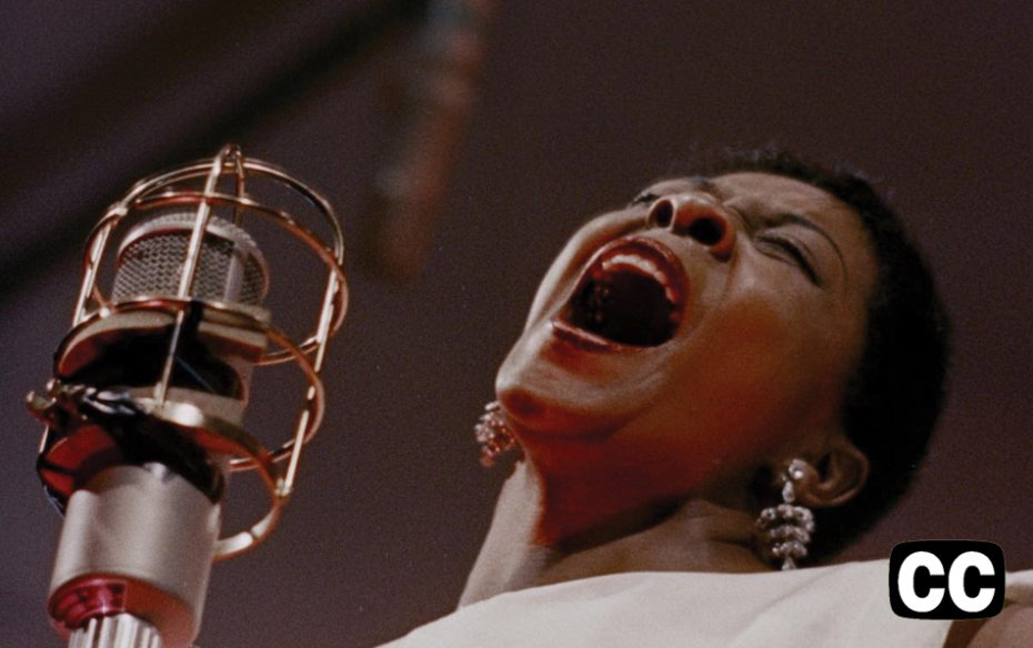 Watch trailer. Dinah Washington singing in front of a microphone.