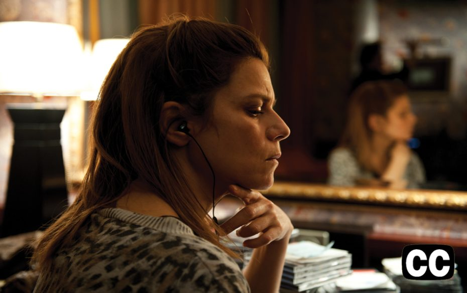 Watch trailer.  A woman, sitting in front of her reflection in a mirror, listening intently to earphones.