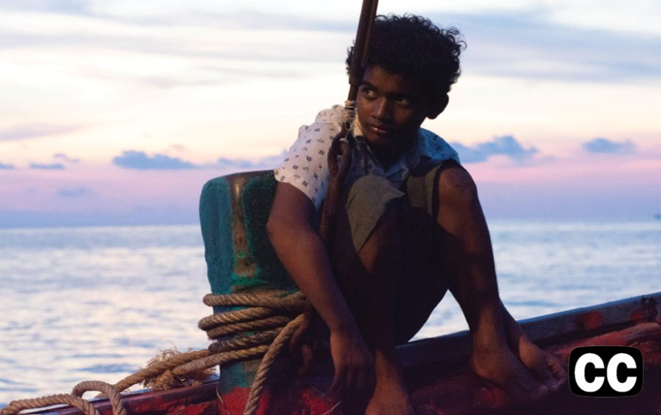 Teenaged cambodian boy crouched on the edge of on a fishing boat