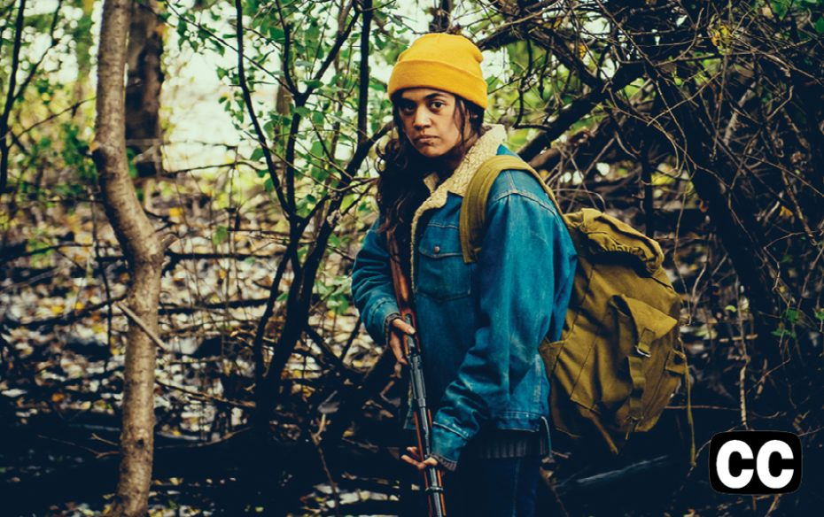 A female hiker, with demin jacket and yellow hat and backpack, in the woods holding a rifle.