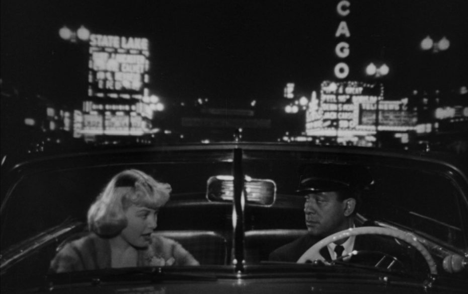 A blonde woman and black chauffeur driving a car at nights with the backdrop of 1950s downtown Chicago.
