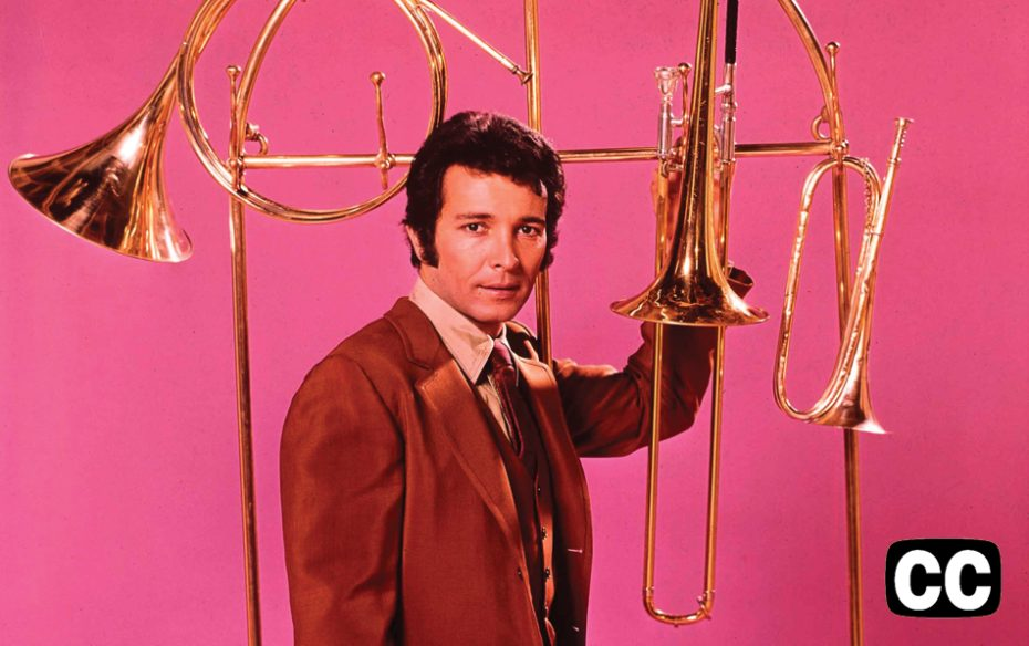 Herb Alpert against a bright pink backgrount wih various horn instruments in a grid pattern.
