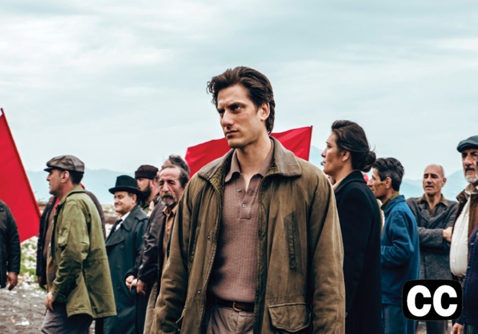 Film still with main character, Martin Eden, wearing a leather jacket, in the forefront, and a group of adults, marching with red flags, in the background.