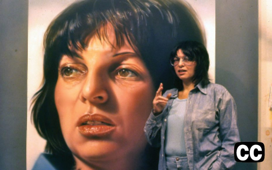 Artist Audrey Flack standng in front of a self portrait.