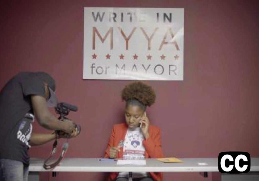 "Woman on cell phone being photographed, sitting at table underneath a sign that reads ""WRITE IN MYYA FOR MAYOR"""