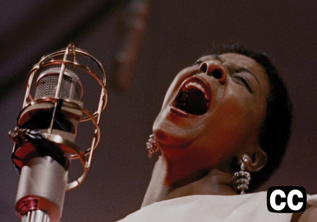Dinah Washington singing in front of a microphone.