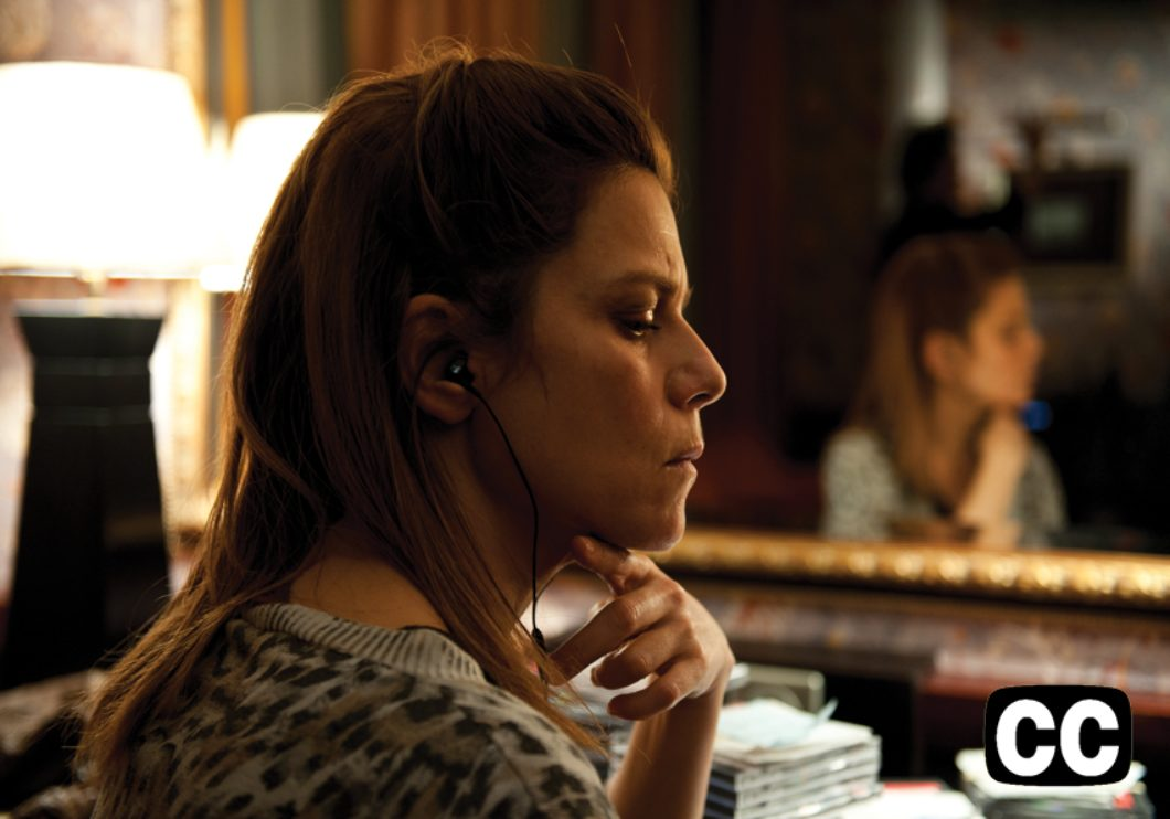 A woman, sitting in front of her reflection in a mirror, listening intently to earphones.