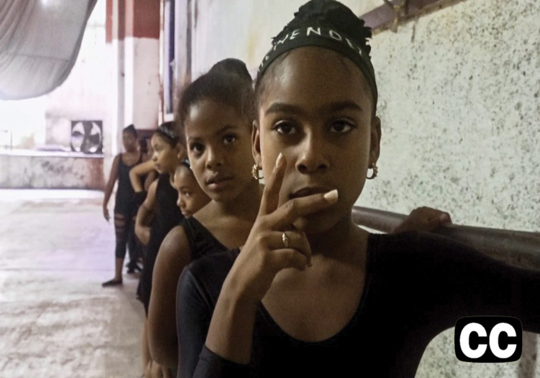 A group of dark-skinned girls in leotards lined up at the dance barre.