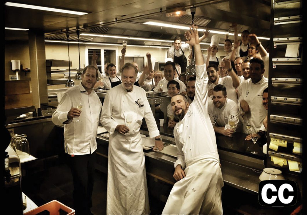A group of jubilant chefs and workers in a restaurant kitchen