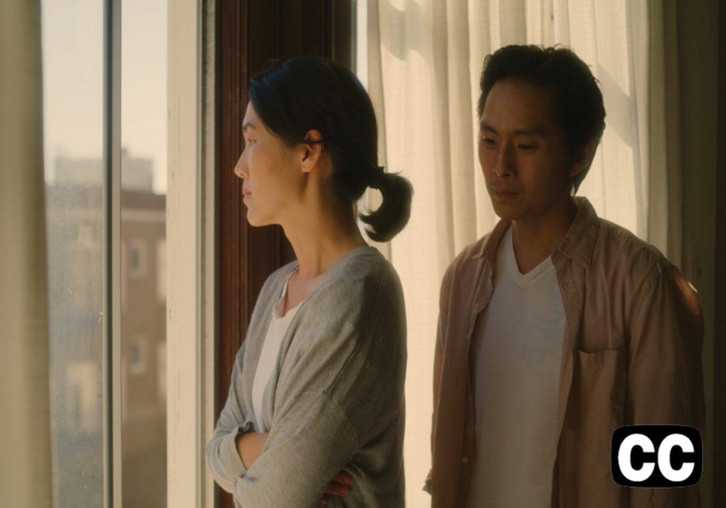 A Korean mother and son standing by a window with a city view.