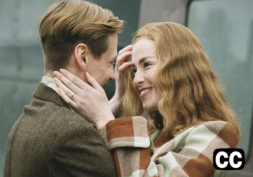 Close up of a young European couple smiling and embracing, outdoors in winter coats.