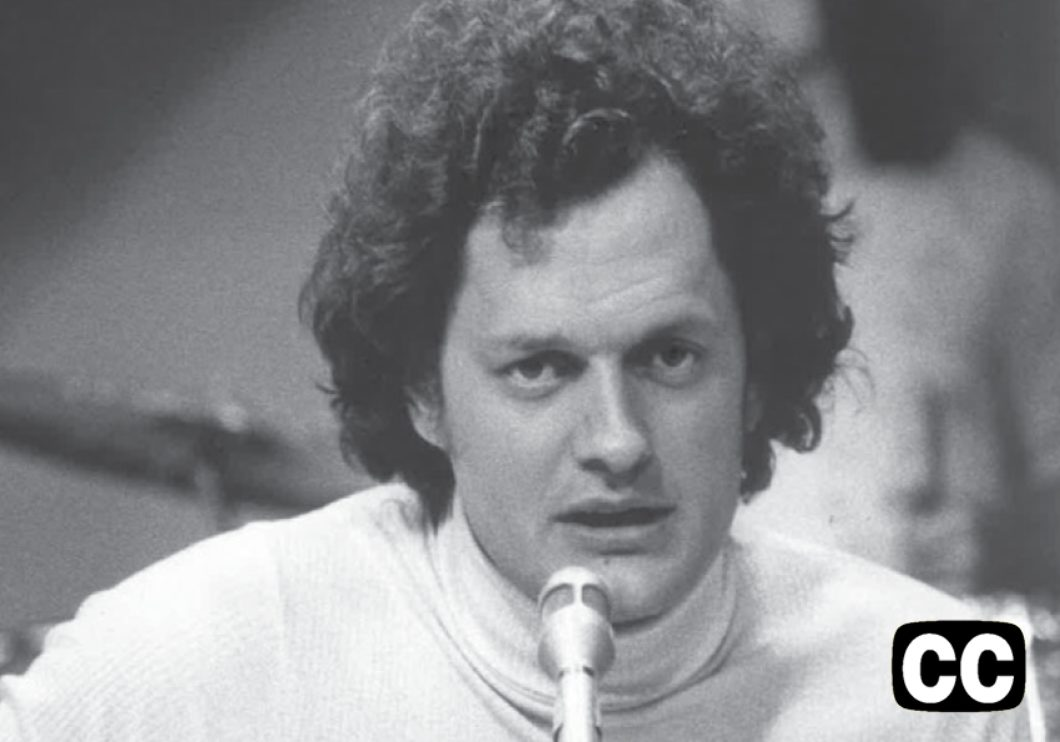 Black and white photo of a young Harry Chapin singing into a microphone.