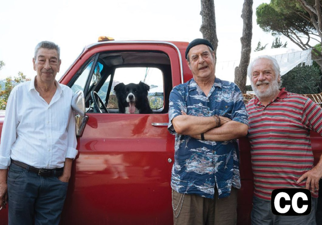 Three men in their 70s leaning casually against a red pick-up truck.  A dog looks out the open front window.
