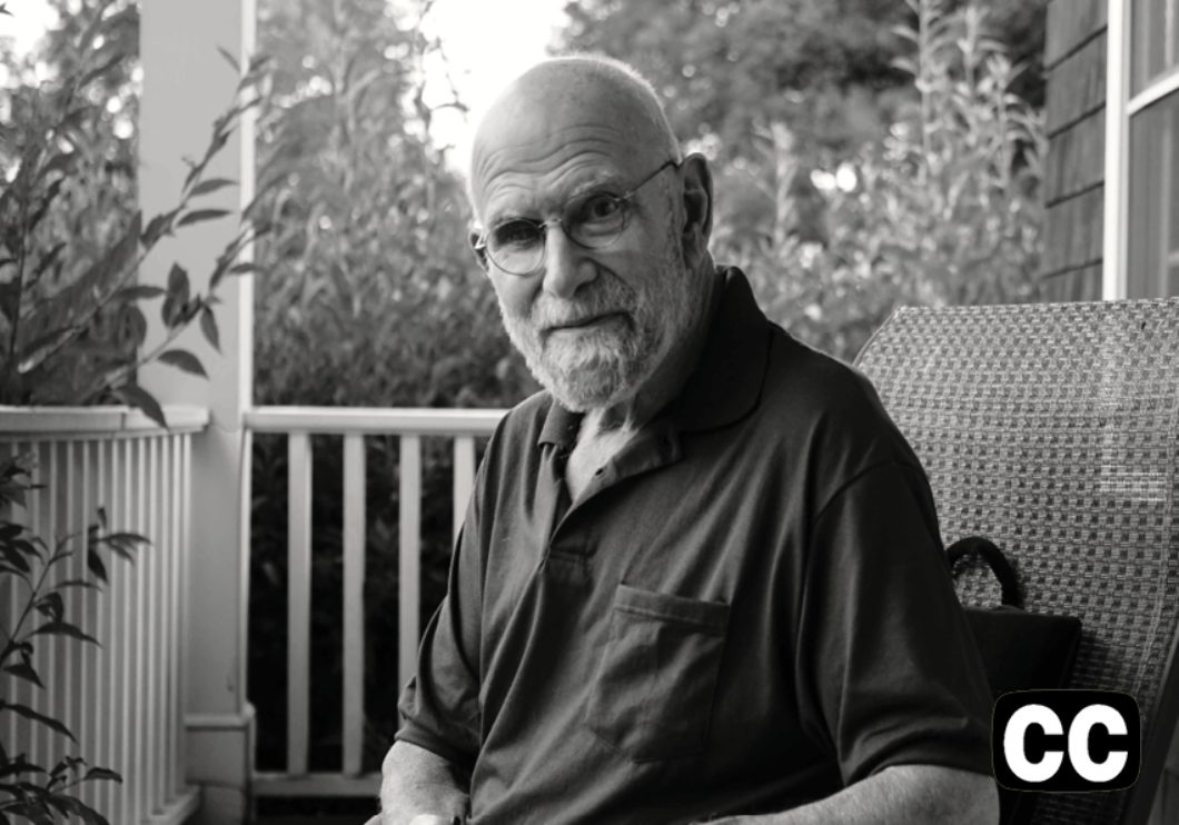 Black-and-white photo of Oliver Sacks sitting on an idyllic front porch.