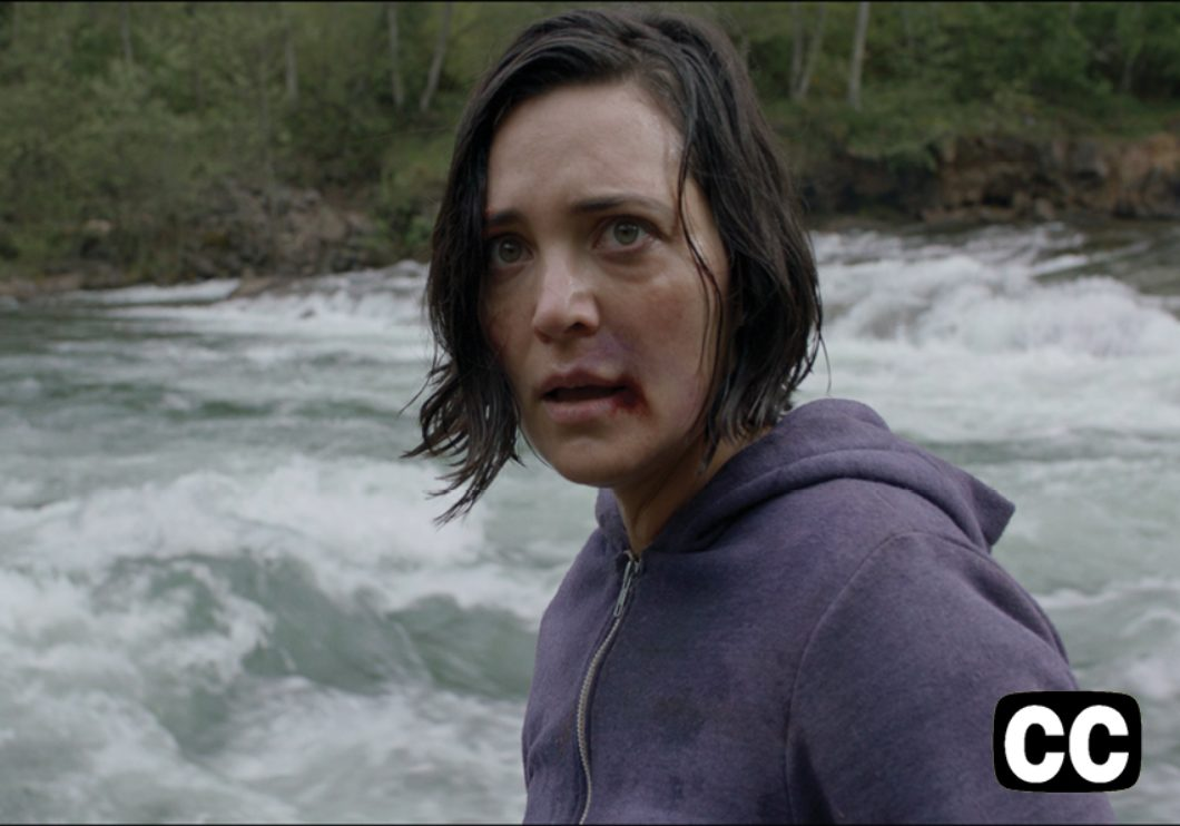 Woman with a bruised face and frightened look with river rapids in the background.