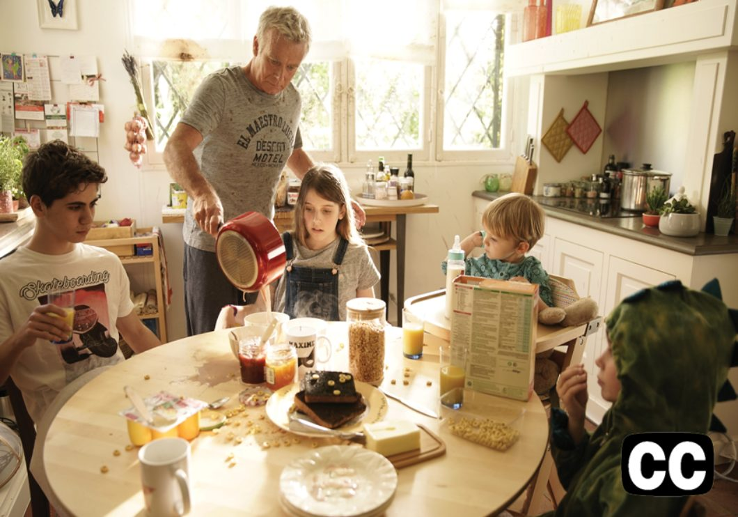 Kitchen scene with dad holding a red pot with four children around the table of various ages.