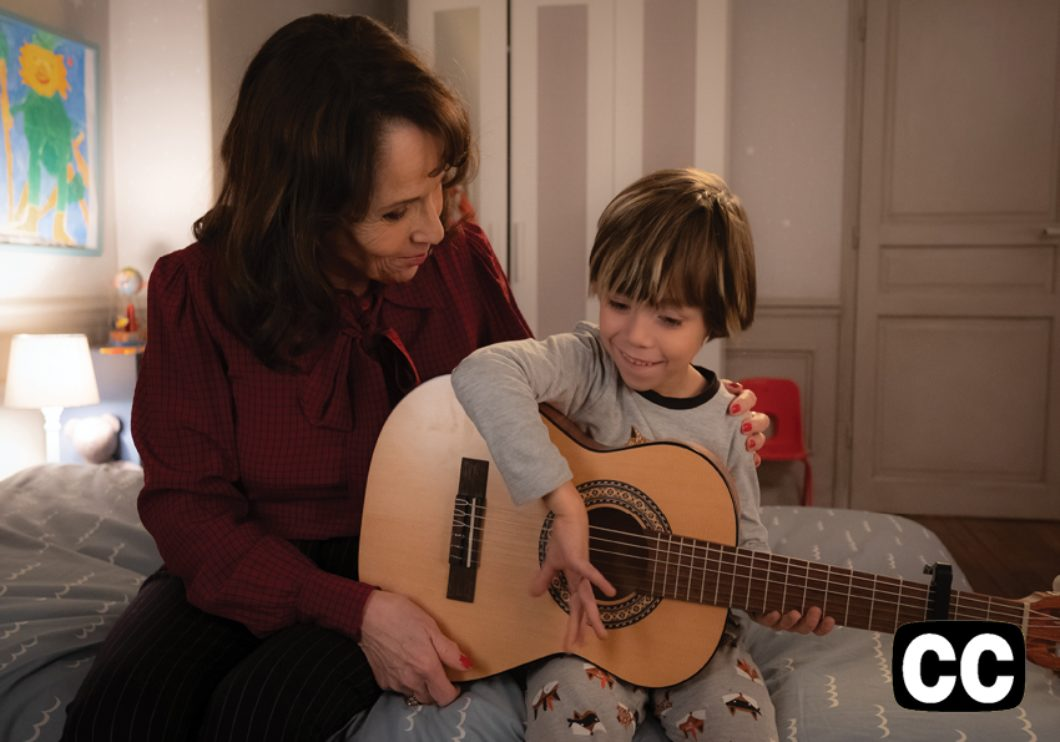 A grandmother and a young boy with a guitar, sitting on the child's bed.