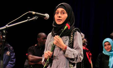 A young woman wearing a hijab stands on stage near a microphone.