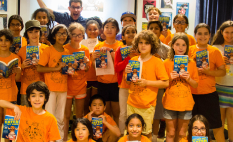 A group of Thalia Book Club camp kids in orange t-shirts hold up books.